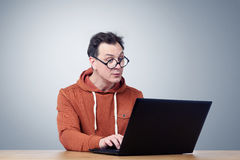 Programmer in glasses with laptop Stock Images