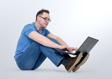 Programmer in glasses working on a laptop and sitting on the floor Stock Photo