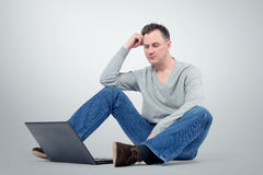 Programmer with laptop sitting on the floor Stock Photography