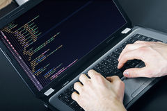 Programmer occupation - writing programming code on laptop Royalty Free Stock Images