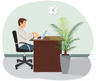 A programmer. A programmer sits in the chair and works on a laptop. A palm tree is on the floor Royalty Free Stock Photography