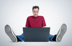 Programmer sitting on the floor in front of a laptop Royalty Free Stock Images