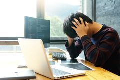 Programmer work with Developing programming. And coding try to solve the problem so serious and sometime feel headache stock photography