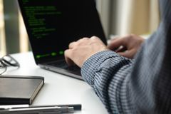 Programmer working on laptop at office. Focus on programming code stock photos