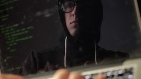 Double exposure: man hacker in glasses working at a laptop. Programmer writes green code reflection in the monitor. Programmer writes green code reflection in stock video footage