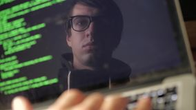 Double exposure: man hacker in glasses working at a laptop. Programmer writes green code reflection in the monitor. Programmer writes green code reflection in stock footage