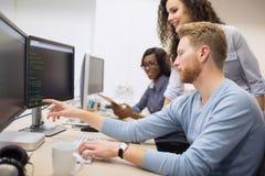 Programmerare som arbetar i ett framkallande företag för programvara royaltyfri bild