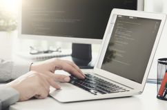Programmerare som arbetar upptagen programvara som framkallar i företagskontor Royaltyfri Foto