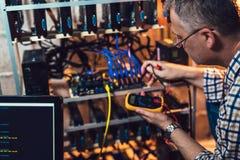 Programmerare som rymmer en wattmeter som mäter cryptocurrencyen som bryter riggen royaltyfria foton