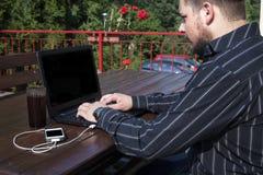 Programmerare som utomhus arbetar på en kod Fotografering för Bildbyråer