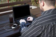 Programmerare som utomhus arbetar på en kod royaltyfri foto