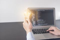 Programmerarehand för ung kvinna som rymmer den ljusa kulan, kvinnahänder som kodifierar och programmerar på skärmbärbara datorn, arkivfoton