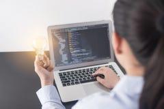 Programmerarehand för ung kvinna som rymmer den ljusa kulan, kvinnahänder som kodifierar och programmerar på skärmbärbara datorn, royaltyfria foton