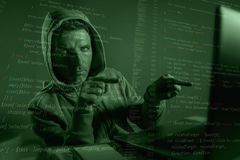Programmerareman i skrivande in kod för hoodiedataintrångsystem som pekar till bärbara datorn som hackar och olagligt tillträde f arkivbilder