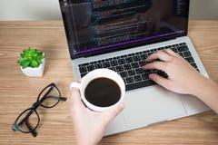 Programmerarens h?nder analyserar n?gon system och information p? datorsk?rmen, medan dricka kaffe p? skrivbordet royaltyfria foton
