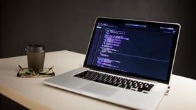 Programmerares arbetsplats, b?rbar dator med projektkod Utveckling av websites och applikationer arkivfoton