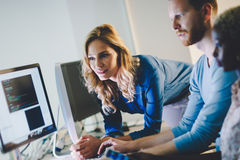 Programmers cooperating at information technology company. Programmers cooperating at  IT company developing apps Royalty Free Stock Photo