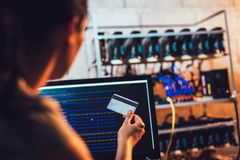 Programmers are watching the bitcoin rate and holding credit card. Programmers are watching the bitcoin exchange rate and holding credit card Royalty Free Stock Image