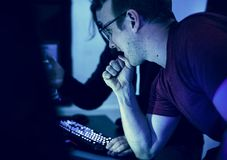 Programmers working on computer program. In dark Royalty Free Stock Photography
