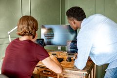 Programmers working with program code. Two young programmers working with program code sitting at the workplace with three monitors in the office on the green stock image
