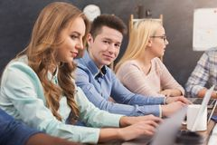 Programmers working in software developing company. Team of young programmers working in software developing company, typing on laptops, testing new games or stock photos