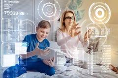 Programmeur calme travaillant dans la réalité virtuelle et son fils presque jouant image libre de droits