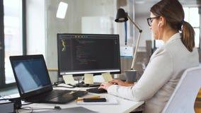 Programmeur dans des écouteurs travaillant sur l'ordinateur banque de vidéos