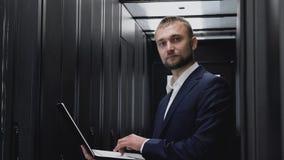 Programmeur die van de succes de bezige ingenieur met servers en glimlach werken stock video
