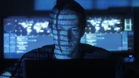 Programmeur masculin de pirate informatique fonctionnant à l'ordinateur tandis que les caractères de code bleus réfléchissent sur banque de vidéos