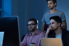 Programmeurs réfléchis beaux regardant l'écran d'ordinateur Photo stock
