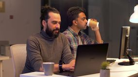 Programmierer mit dem Kaffee, der an den Computern arbeitet stock footage