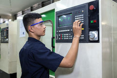 Programming CNC machine. Man programming CNC machine in the factory Stock Photos