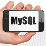 Programming concept: Hand Holding Smartphone with MySQL on display