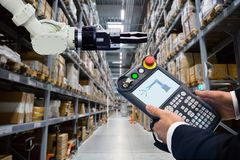 Programming robot with robotic arm in warehouse royalty free stock image