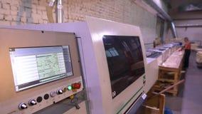 Programmmonitor auf der CNC-Maschine, Leute arbeiten im Hintergrund stock footage