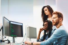 Programvaruteknikerer som arbetar på projekt och programmerar i företag royaltyfri foto