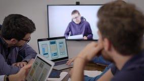 Programvaruutvecklare för mobiltelefoner lyssnar på chefsspecialist genom videosamtal i konferensrum stock video