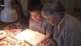 Prograndmother с больш-внуком прочитало на книге таблицы сток-видео