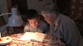 The prograndmother with the great-grandson read at the table  book stock video