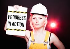 Progress in action sign placed on information board, worker woman Stock Image