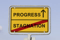 Progress asnd stagnation. Blue sky behind a yellow city limit or place name sign informing with an arrow that you are on the way to progress and leaving stock photos