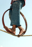 Progress on Balance. A closeup view of the feet of a poor Indian trapeze girl, whose daily living hangs on the balance of her act on the rope. The image also Stock Photo