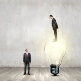 Progress in business. Businessman standing on bulb and looking down at colleague Stock Photography