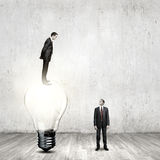 Progress in business. Businessman standing on bulb and looking down at colleague Royalty Free Stock Image