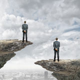 Progress in business. Rear view of businessman standing at rock edge Royalty Free Stock Photos