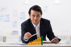 Progress in business. Satisfied businessman looking at ascending bar graph in front of him Royalty Free Stock Photos