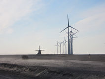 Progress of technology. Old mill and new turbines Stock Photos