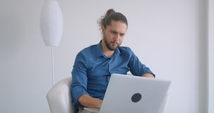 Progressieve freelancer die met laptop zitting in leunstoel in comfortabel en licht bureau werken stock footage