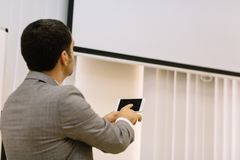 Business man showing presentation on a multimedia projector background. Technology concept. Copy space. Progressive business man showing a presentation on a new royalty free stock photography