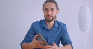 Progressive businessman with ponytail turns on app on tablet and shows vertical green chroma screen to camera in white. Office stock footage